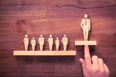 Finger pointing at wooden cutouts of individuals in business attire