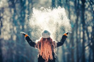 Woman throwing snow into the air