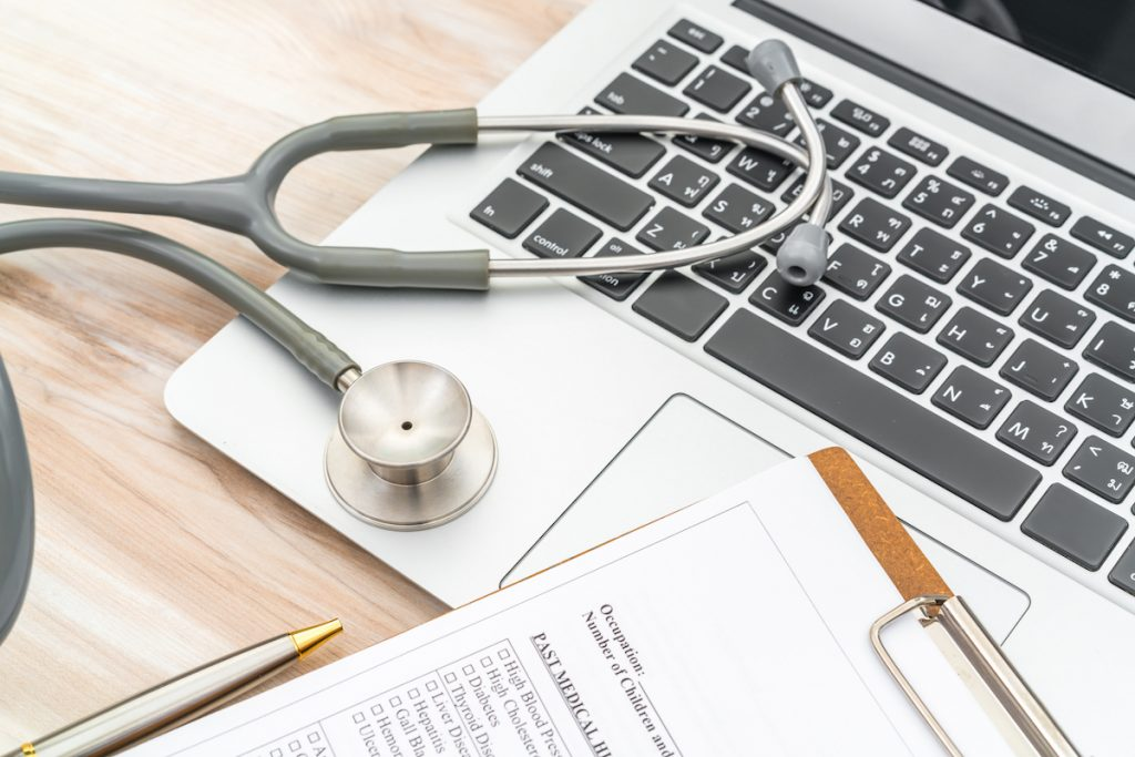 Doctor's stethoscope, documents, and laptop