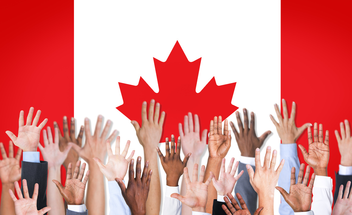 Canadian flag with many different hands infront of it