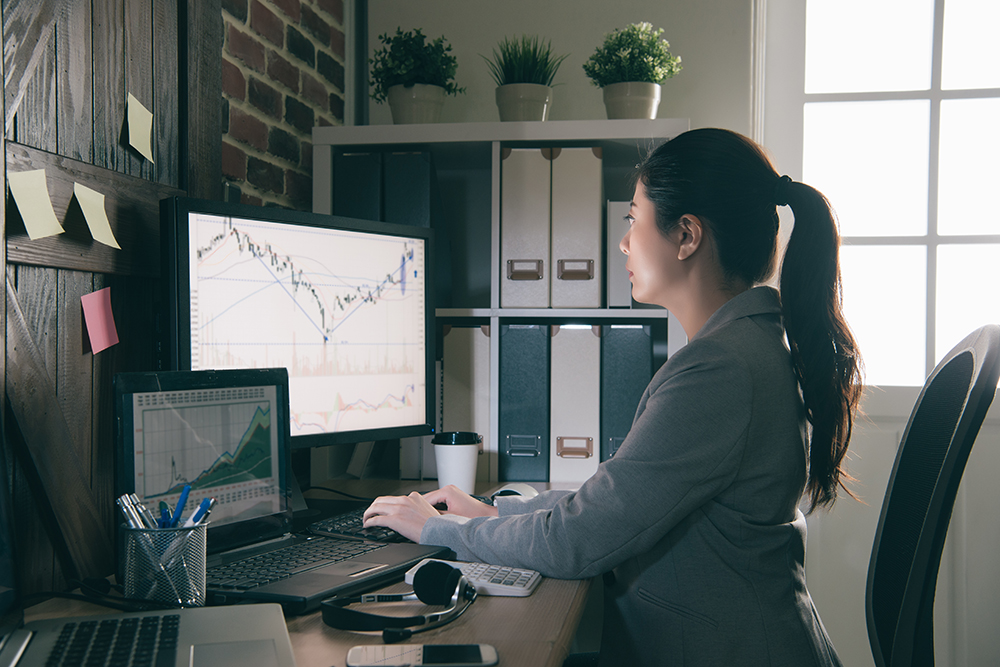 Woman looking at graphs on computer
