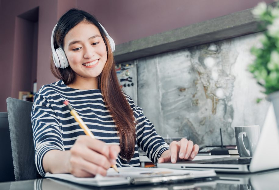 Woman listening to music and studying