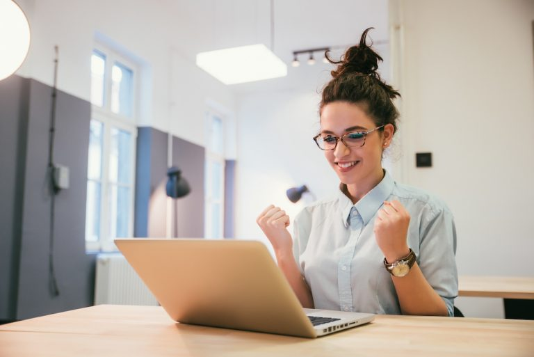 Happy student working on laptop