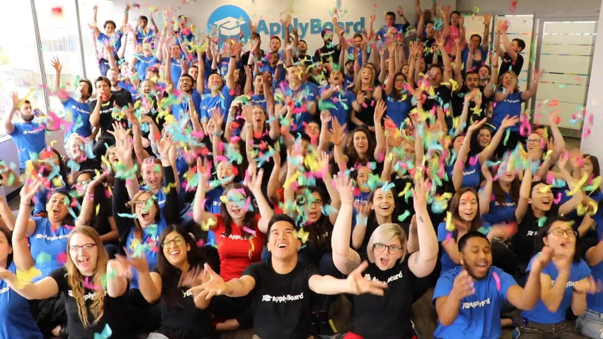 ApplyBoard employees with arms raised