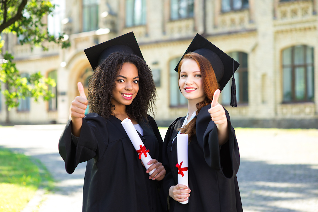 Two female graduates giving thumbs up