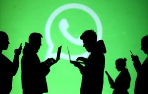 Silhouette of people on laptops and phones against WhatsApp logo