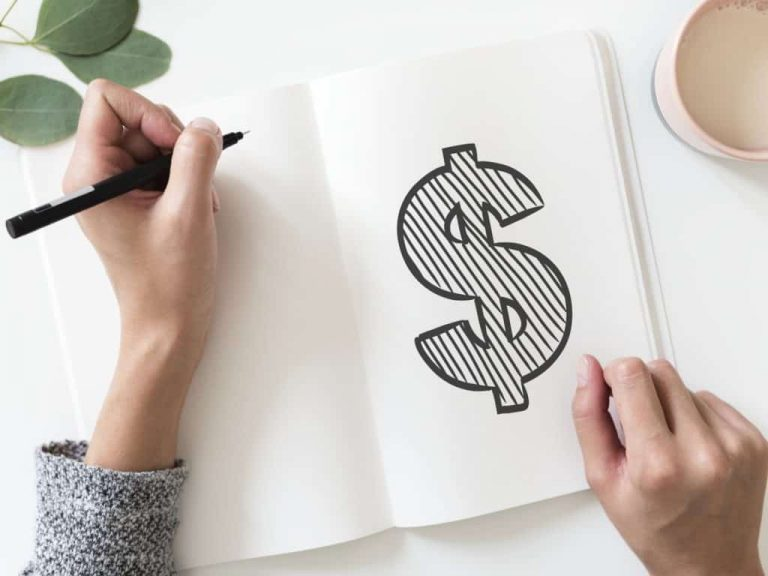 Woman doodling a money sign in journal