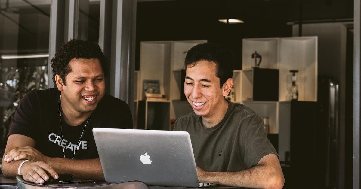 Two men working at laptop