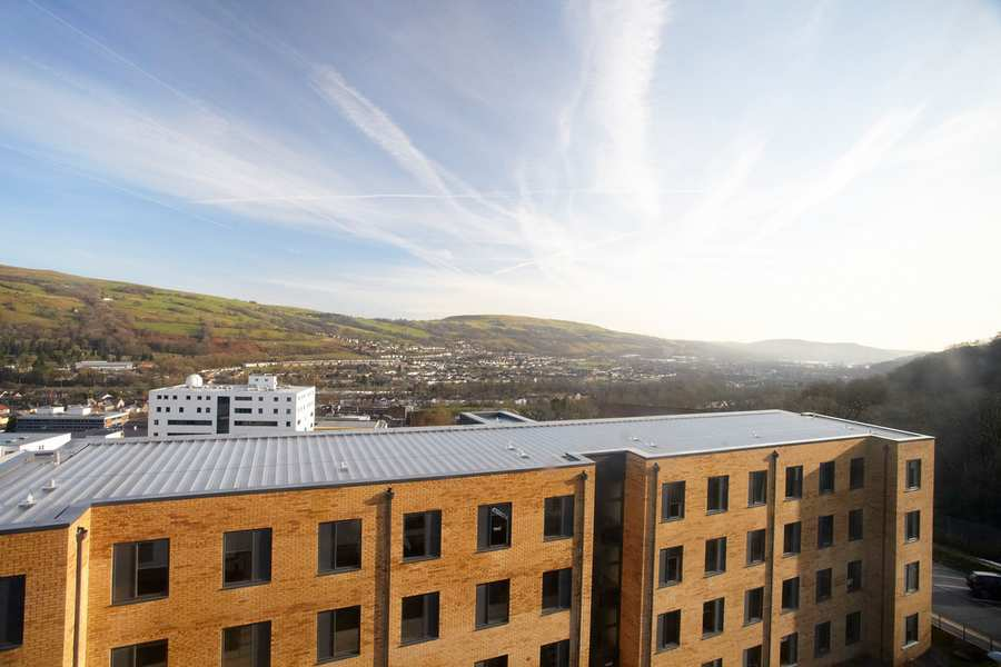 Photograph of sky and hills beyond halls of residence at University of South Wales Treforest campus