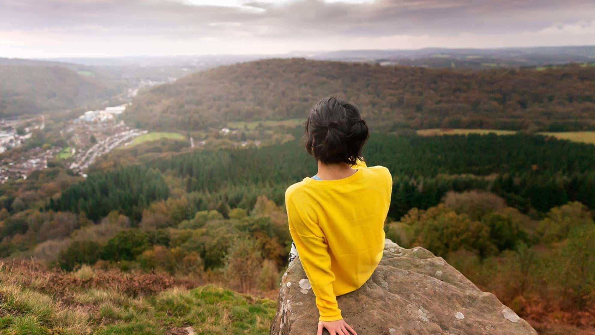 Person sitting on edge of a cliff