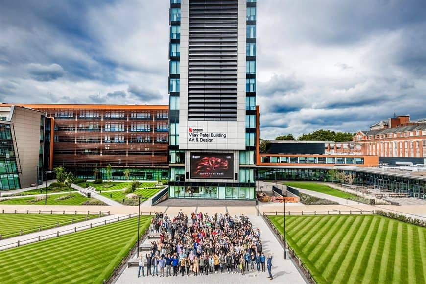 A photo of De Montfort University Leicester's campus with students standing outside.