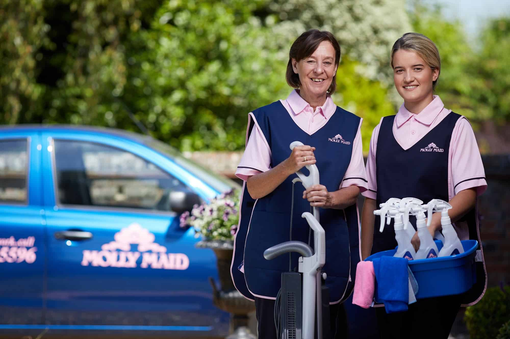 A photo of two Molly Maids with their cleaning supplies.